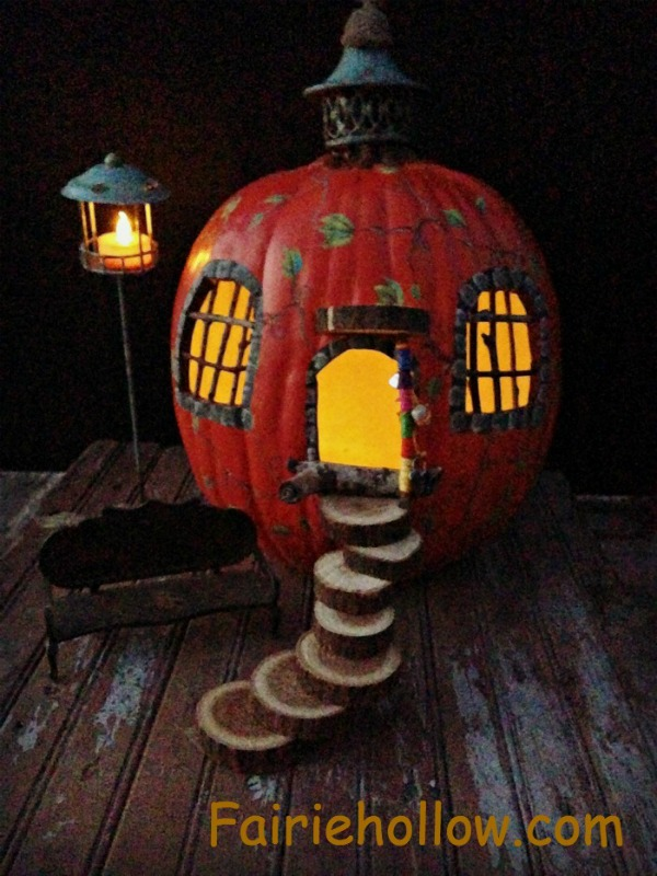 DIY Painted pumpkin fairy house with steps made from sliced branches and steeple made from found objects. fairiehollow.com